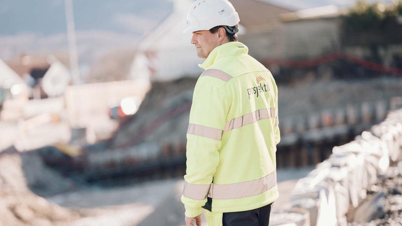 Mann i Prosjektil-jakke inspiserer byggeplass
