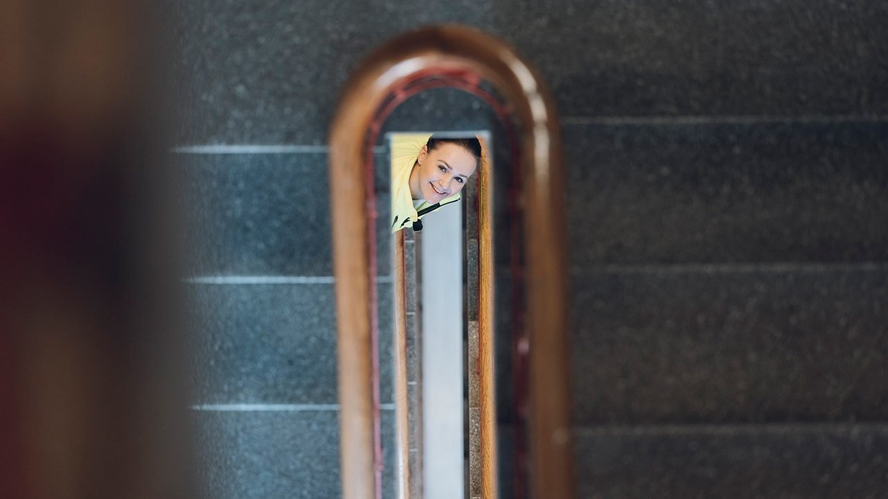 Smilende kvinne titter opp trappeoppgang