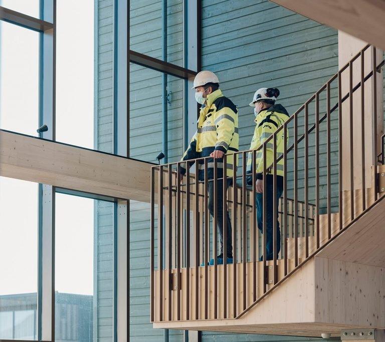 Prosjektadministrasjon - to ansatte står i trapp i stort bygg og ser ut gjennom store vindusflater