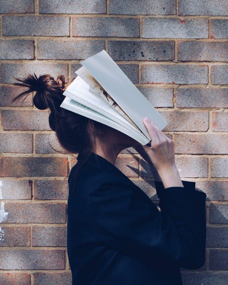 Kvinne holder en åpen bok mot ansiktet