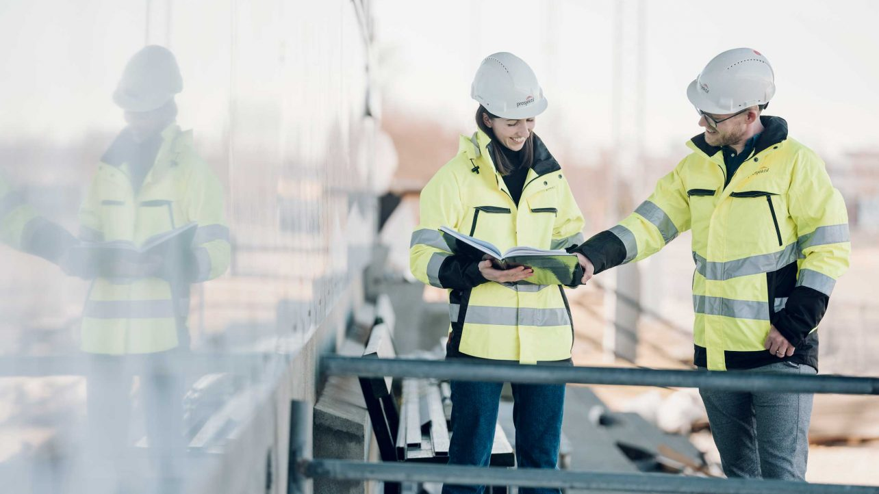 Prosjektil Sør - kvinne og mann på byggeplass. Ser i perm.